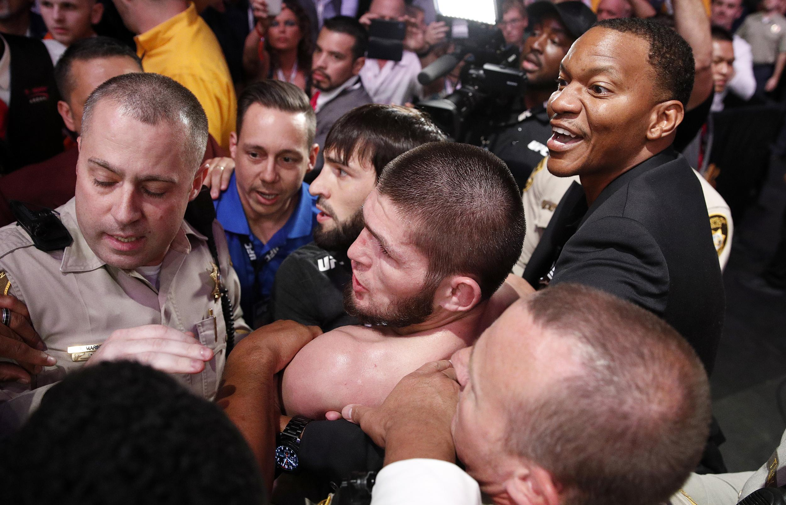 270612253-khabib-nurmagomedov-bottom-center-is-held-back-outside-of-the-cage-after-fighting-conor-mc
